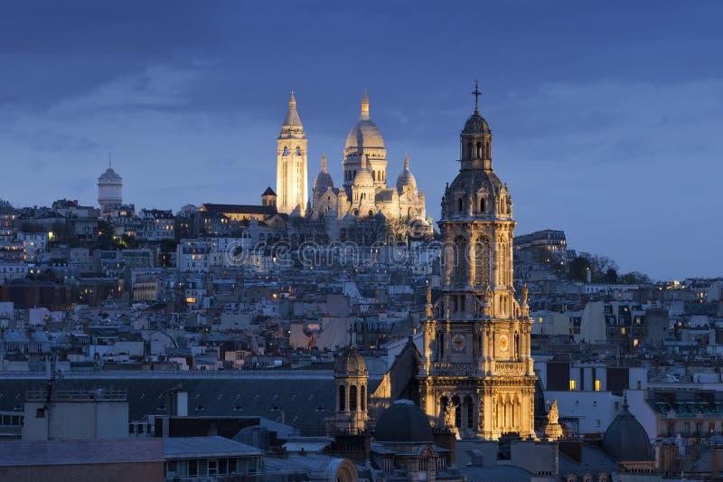 Sacre coeur, Montmartre och Sainte-Trinité på nightinen Paris royaltyfri foto