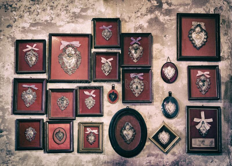 Sacred silver hearts donated by people who received divine grace hanging in a church in Italy. Sacred silver hearts donated by people who received divine grace royalty free stock photo