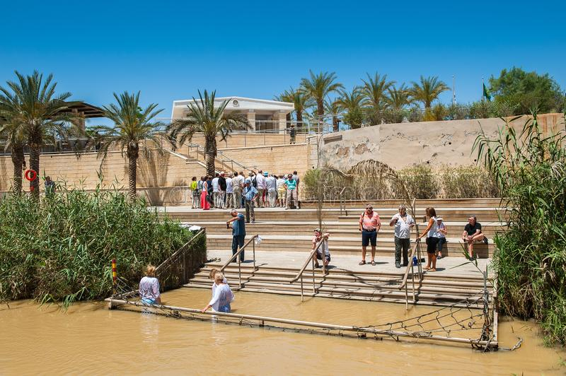 Sacred water of the River Jordan. JESUS CHRIST BAPTISM SITE , ISRAEL - MAY 1, 2014: Unidentified pilgrims near the Sacred water of the River Jordan. River where royalty free stock photos