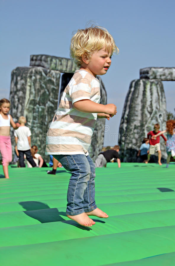 Sacrilege inflatable stonehenge. Young boy bouncing on sacrilege, an inflatable stonehenge by jeremy deller in whitstable on 5th september 2012, a festival of stock photography