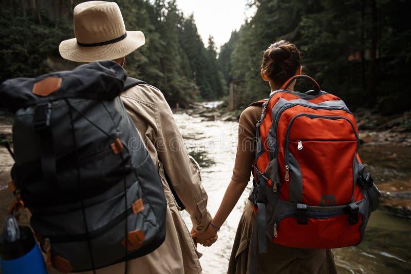 Sacs à dos de couples actifs et mains de transport de se tenir tout en voyageant photos stock