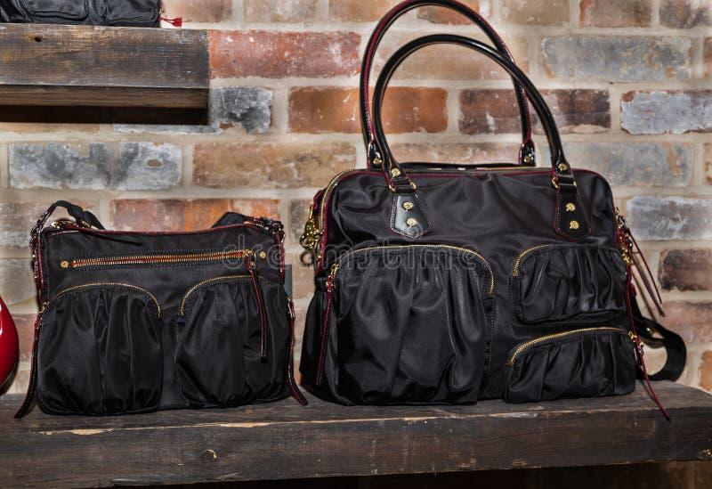 sacs à la mode et élégants de noir de femme, bourse se tenant sur l'étagère en bois sur le vieux fond de brique photos libres de droits