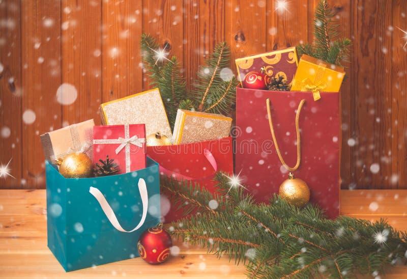 Sacs à provisions avec des cadeaux, des boules de Noël et des branches de sapin images libres de droits