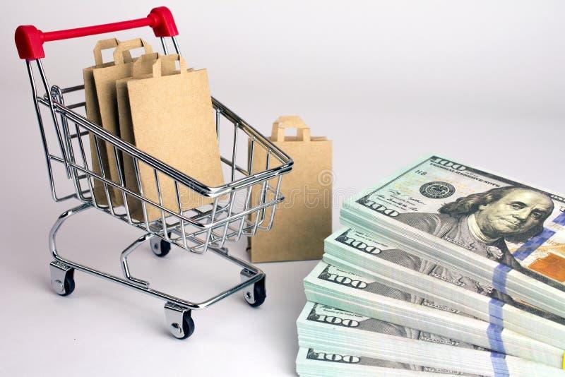 Sacs à provisions dans des paquets de chariot de supermarché de dollars images libres de droits