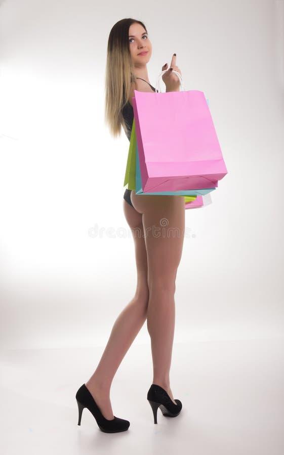Sacs à provisions de fixation de femme d'achats Plan rapproché de belles jambes de femmes dans un maillot de bain et des talons h image libre de droits
