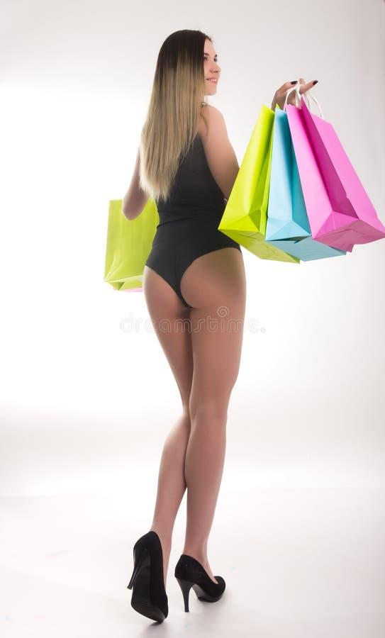 Sacs à provisions de fixation de femme d'achats Plan rapproché de belles jambes de femmes dans un maillot de bain et des talons h image stock