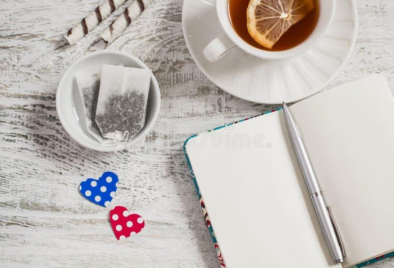 Sacs à thé faits maison de Saint-Valentin, thé avec le citron et carnet ouvert de blanc photo stock