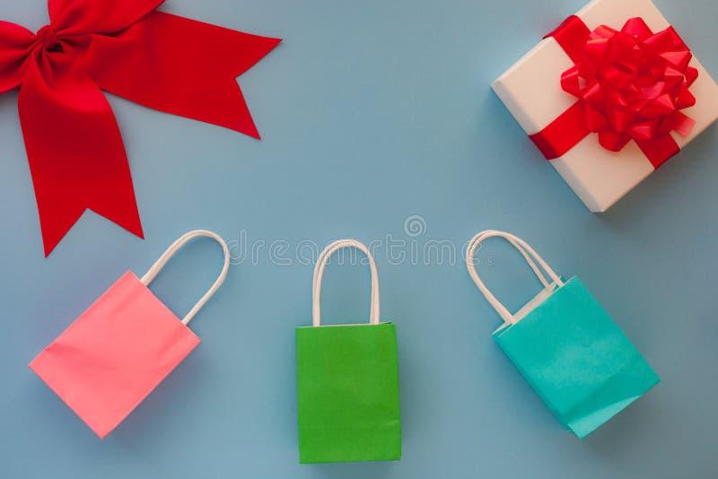 Sacs de papier colorés de cadeau et boîte-cadeau blanc avec l'arc et la nervure rouges images stock