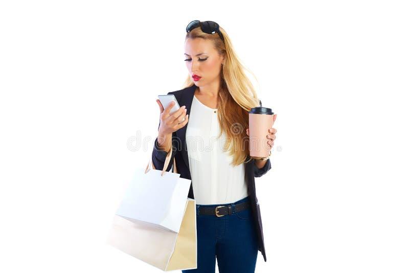 Sacs et smartphone shopaholic blonds de femme photographie stock libre de droits