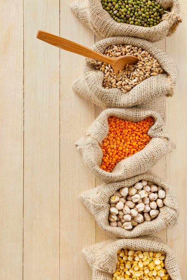 Sacs hessois avec des grains sur la table en bois photographie stock libre de droits