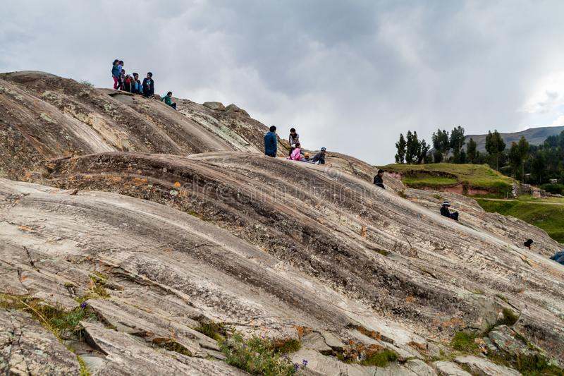 SACSAYWAMAN PERU, MAJ, - 24, 2015: Ludzie z dziećmi na naturalnych obruszeniach przy Inca ruinami Sacsaywaman blisko Cuzco, Na zdjęcie royalty free