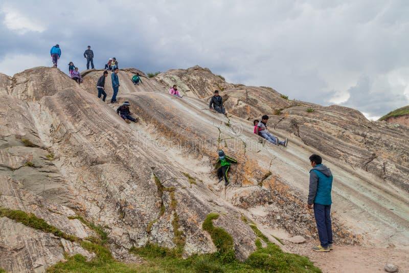 SACSAYWAMAN PERU, MAJ, - 24, 2015: Ludzie z dziećmi na naturalnych obruszeniach przy Inca ruinami Sacsaywaman blisko Cuzco, Na fotografia stock