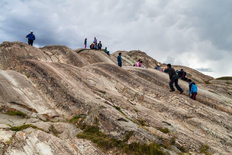 SACSAYWAMAN PERU, MAJ, - 24, 2015: Ludzie z dziećmi na naturalnych obruszeniach przy Inca ruinami Sacsaywaman blisko Cuzco, Na obrazy stock