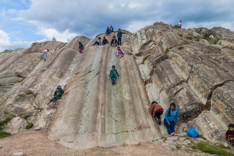 SACSAYWAMAN PERU, MAJ, - 24, 2015: Ludzie z dziećmi na naturalnych obruszeniach przy Inca ruinami Sacsaywaman blisko Cuzco, Na obraz royalty free