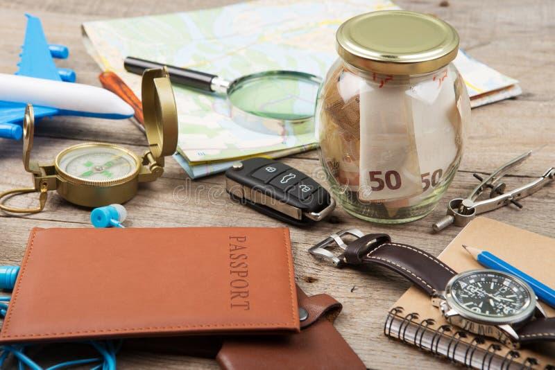 Sacuda con el dinero para el viaje, los mapas, el pasaporte, y la otra materia para la aventura en la tabla imagenes de archivo
