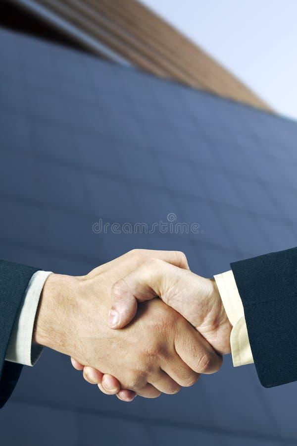 Sacudida de las manos delante de un edificio imagen de archivo