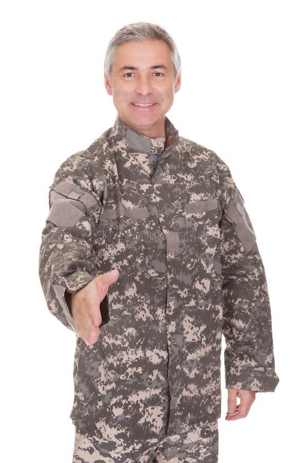 Sacudida madura de Extending Hand To del soldado fotografía de archivo