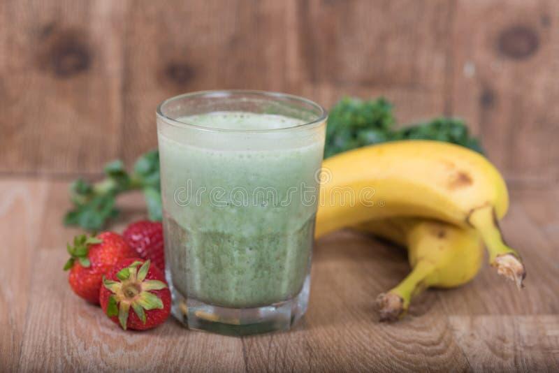 Sacudida verde del smoothie con verdes frescos y frutas imagenes de archivo