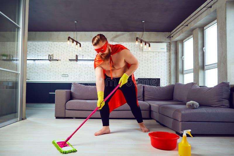 Sadło, śmieszny mężczyzna w bohatera kostiumu czyści dom obraz stock