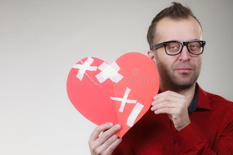 Sad adult man holding broken heart royalty free stock photo