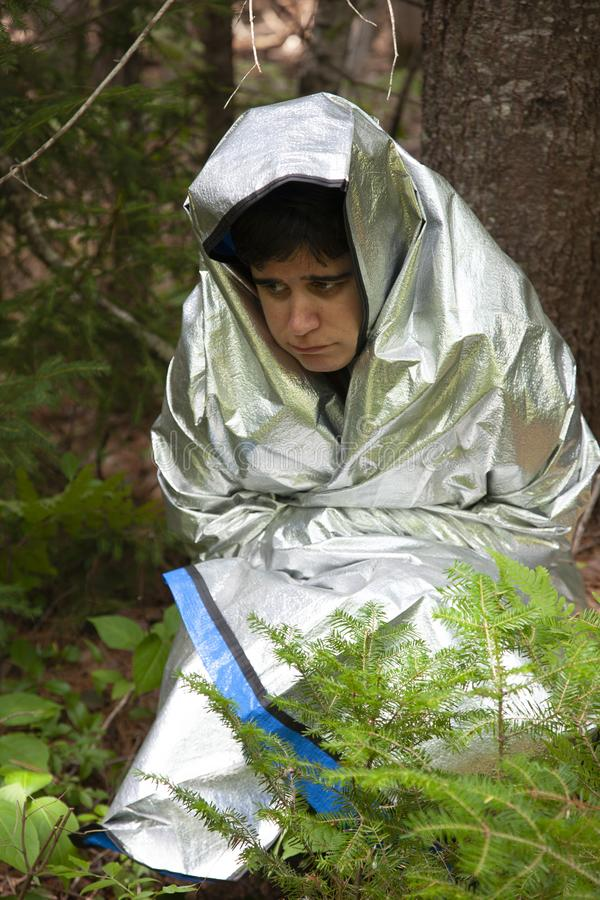 Sad and afraid while lost. Person wrapped in a tinfoil blanket looks scared, cold and lost in the woods stock photography