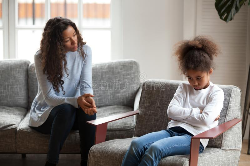 Sad African American girl avoid talking to mom. Upset small African American girl feel hurt avoid talking to young mom making peace, offended preschool mixed stock images