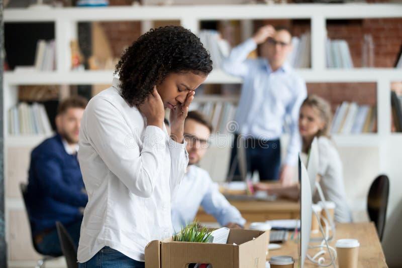 Sad african female employee packing belongings in box got fired. Sad african female young employee packing belongings in box at workplace got fired from job stock image