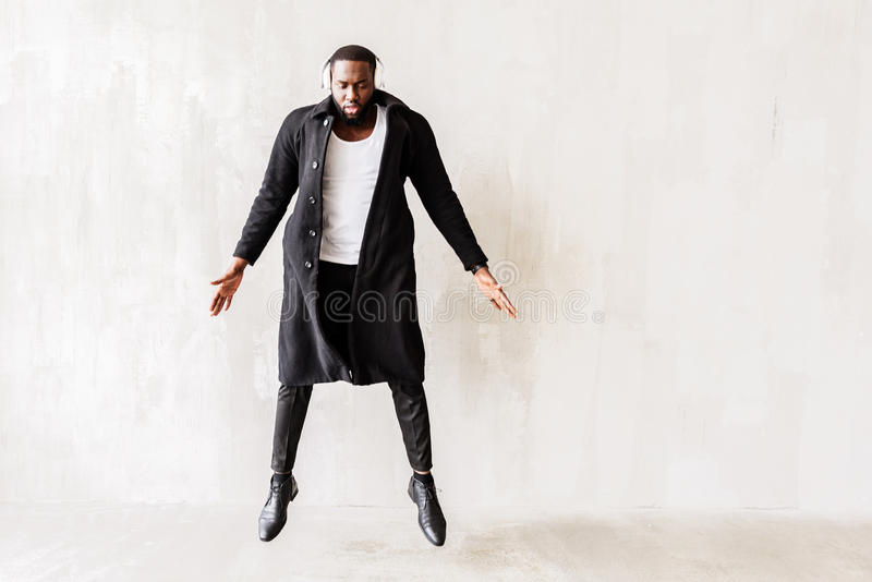 Sad african handsome man dressed in black long unbutton coat royalty free stock photos