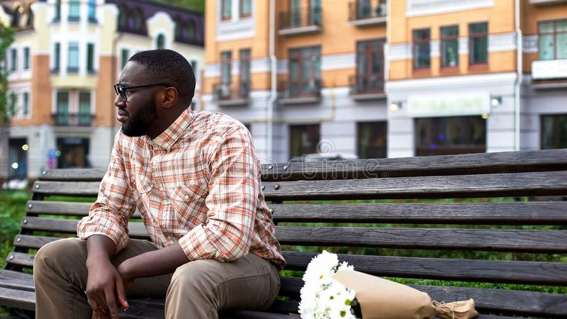 Sad african man sitting lonely on city bench with flower bouquet, failed date royalty free stock image