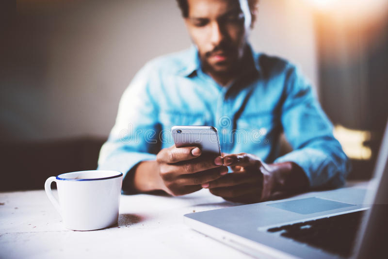 Sad African man using smartphone while sitting at the wooden table his modern home.Concept of young people working with stock photography