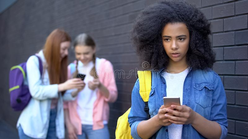 Sad african schoolgirl reading humiliating message, cyber bullying embarrassment. Stock photo royalty free stock images