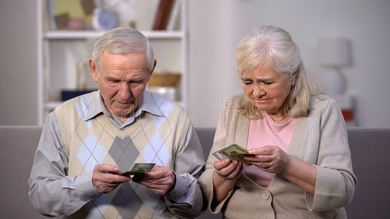Sad aged couple holding few dollar banknotes, lack of money, social problem. Stock photo stock image