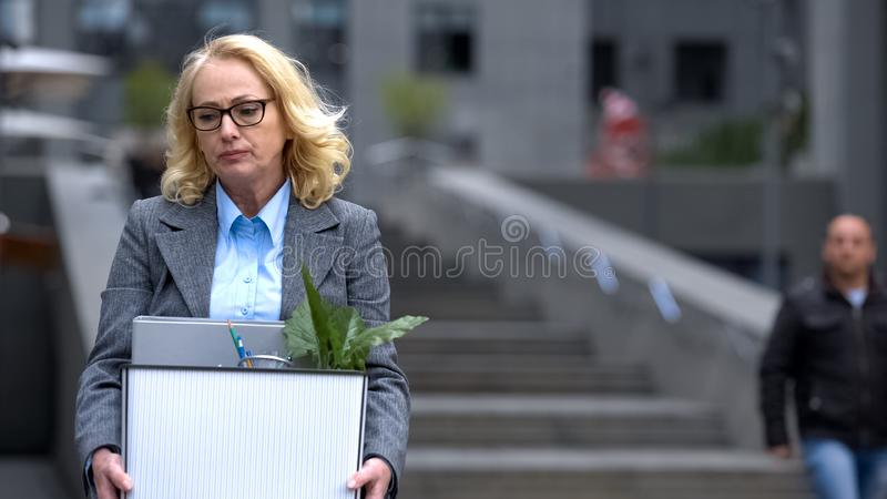 Sad aged manager holding stuff box outside office building, company dismissal. Stock photo royalty free stock image