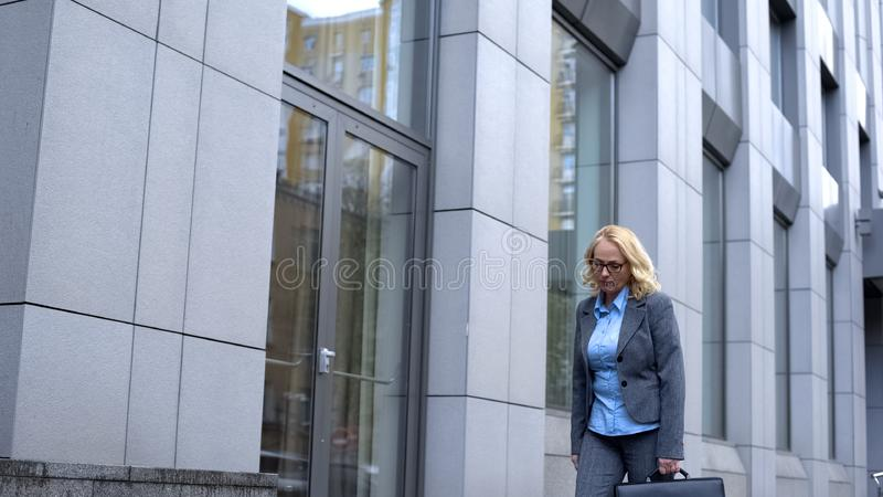 Sad aged woman getting work walking along office building, occupational burnout stock photography