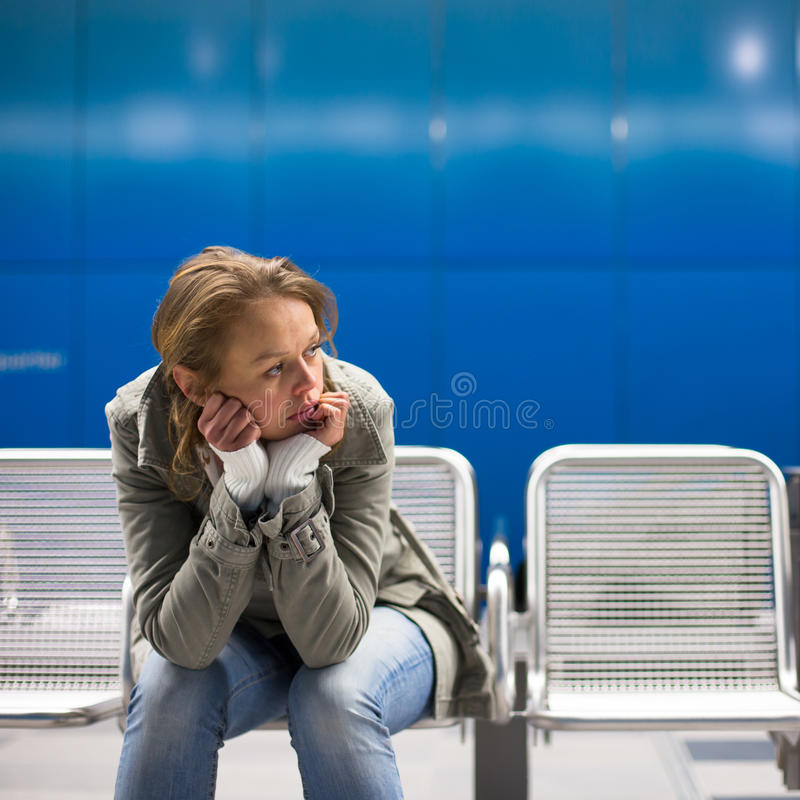 Sad and alone in a big city. Depressed young woman sitting in a metro station, feeling sorrow, regret stock photos