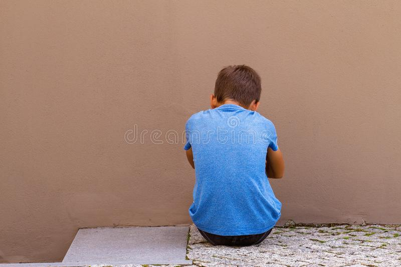 Sad alone boy sitting on the ground behind the wall outdoor royalty free stock photography