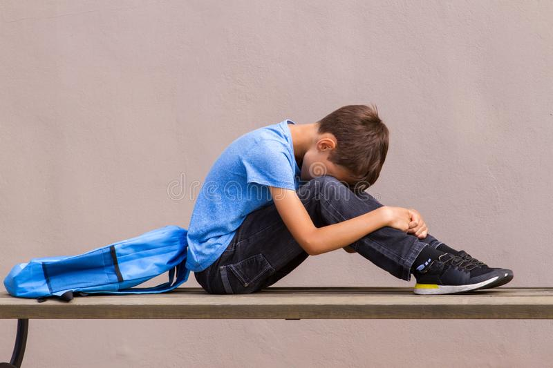 Sad alone child sitting on the bench outdoors stock image