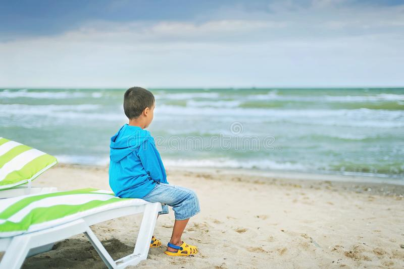 Sad alone kid sitting on beach, looking at sea and thinking. The end of summer. sadness about end of vacation stock photography