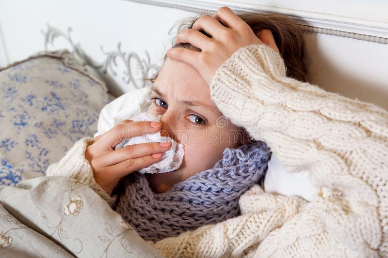 Sad alone young woman in white sweater and blue scarf feeling cold sick and resting home in bed. cleaning her nose, holding her royalty free stock photography