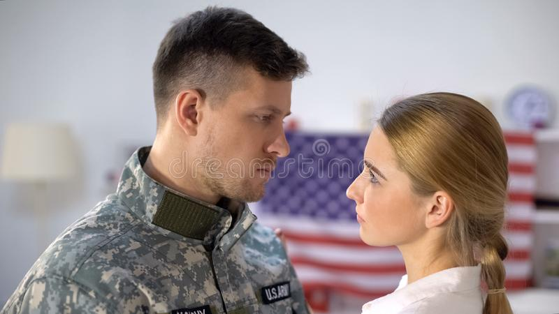 Sad american soldier looking at loving wife, farewell before military service. Stock photo stock image