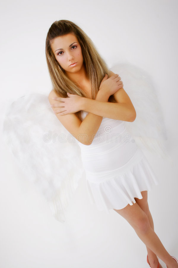 Sad Angel. Sad-looking young woman adorned with wings stock photography