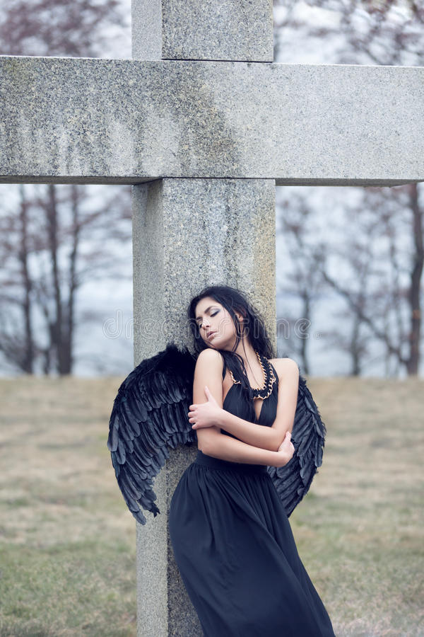 Sad angel. Black sad angel on the cemetery stock image