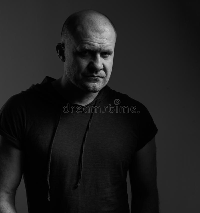 Sad angry crime man with bald head looking mystery and agressive in black shirt on dark grey background. Closeup portrait royalty free stock images