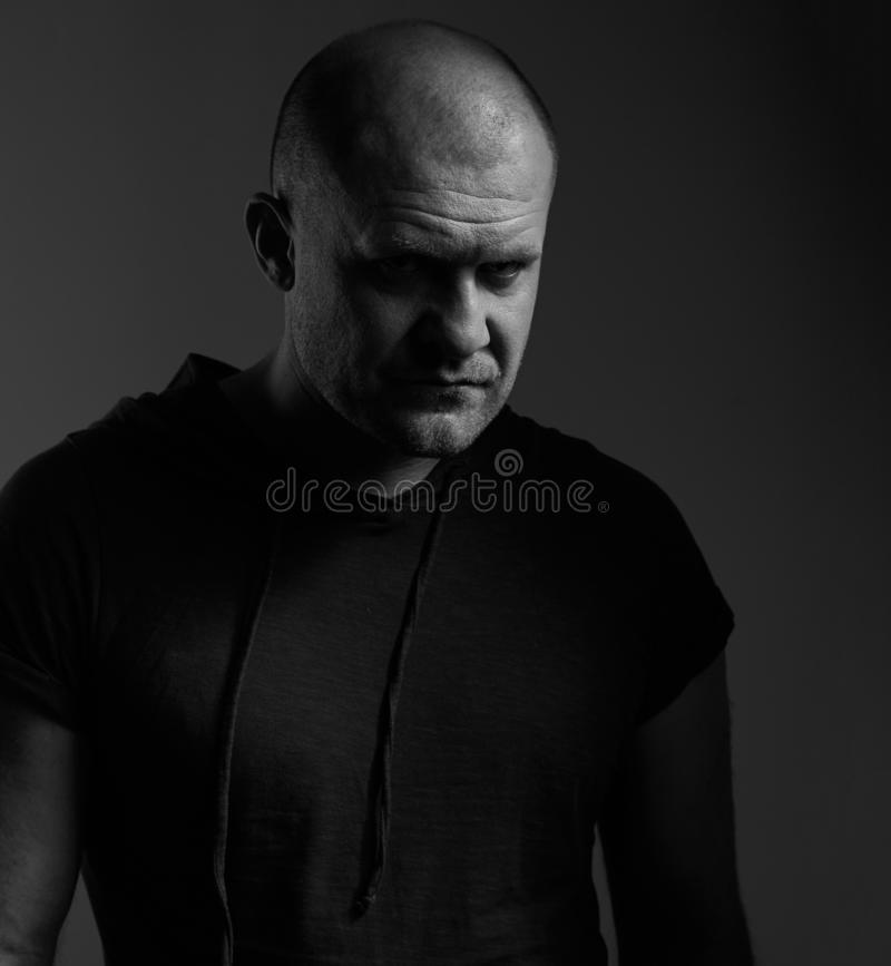 Sad angry crime man with bald head looking mystery and agressive in black shirt on dark grey background. Closeup portrait stock photos