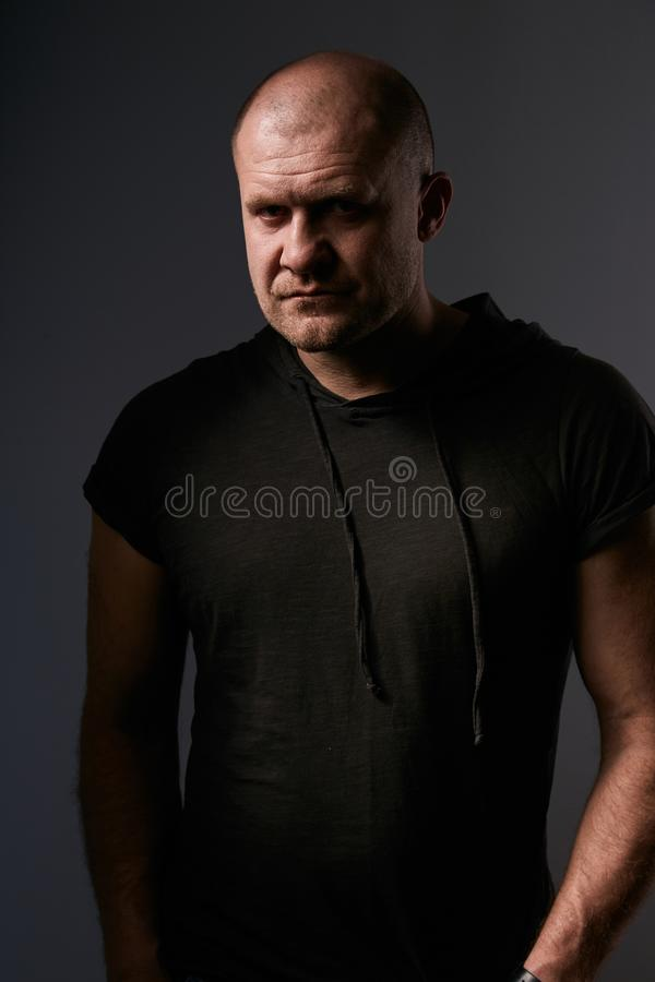 Sad angry crime man with bald head looking mystery and agressive in black shirt on dark grey background. Closeup royalty free stock photography