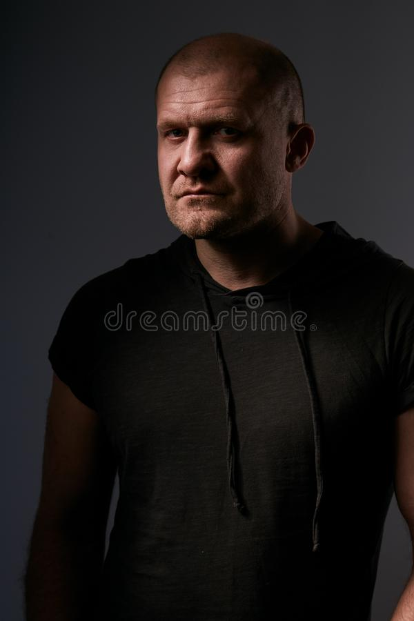 Sad angry crime man with bald head looking mystery and agressive in black shirt on dark grey background. Closeup stock photography