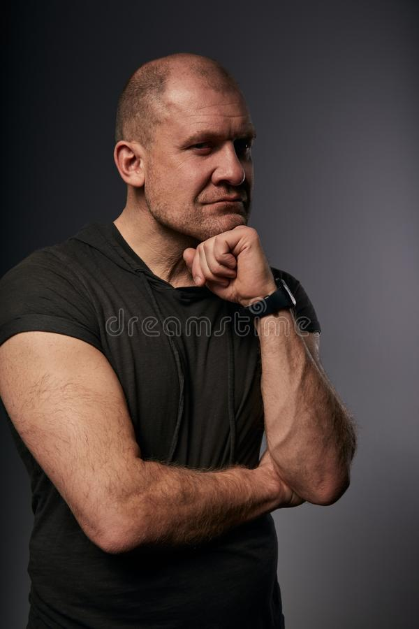 Sad angry crime man with bald head thinking with doubt look in agressive black shirt on dark grey background. Closeup portrait royalty free stock photo