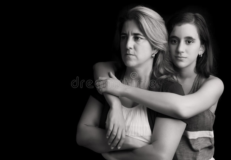 Sad and angry mother with daughter embracing her. Emotional black and white portrait of a sad and angry mother with her teen daughter embracing her royalty free stock photography
