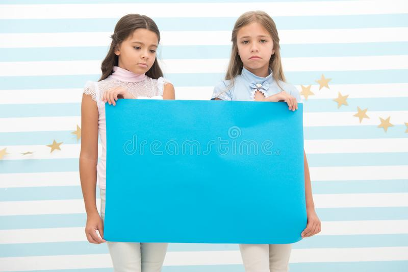 Sad announcement concept. Sorry for bad news. Girl hold advertising banner. Girls kids holding paper banner for. Announcement. Sad disappointed children with royalty free stock photo