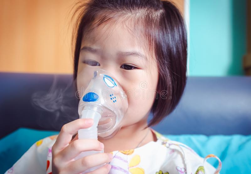 Sad asian child holds a mask vapor inhaler for treatment of asthma. Breathing through a steam nebulizer. royalty free stock photo